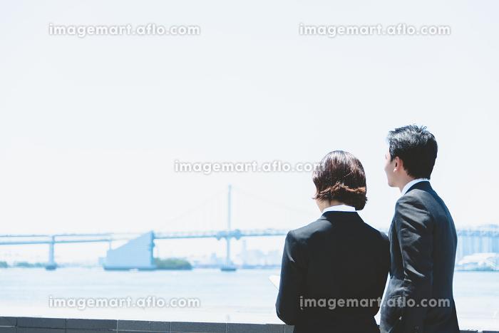 屋外で立って話をする会社員の販売画像