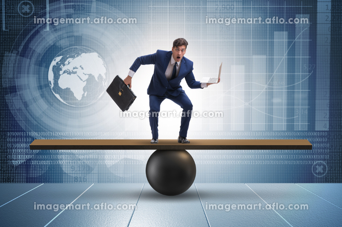 Businessman trying to balance on ball and seesawの販売画像