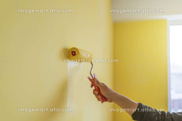 Workman painting the wall in yellow.の販売画像