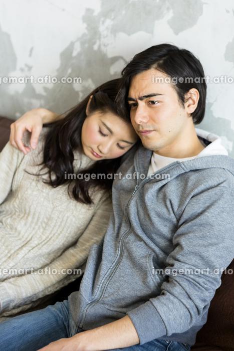 妻の肩を抱く夫