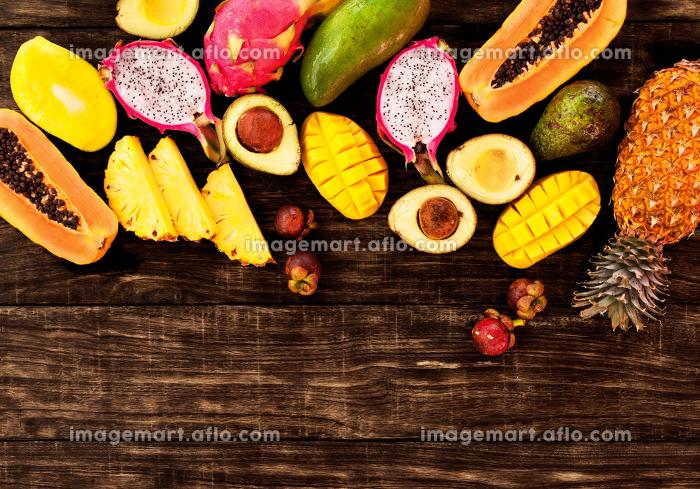 Tropical fruit on dark wooden background, top viewの販売画像