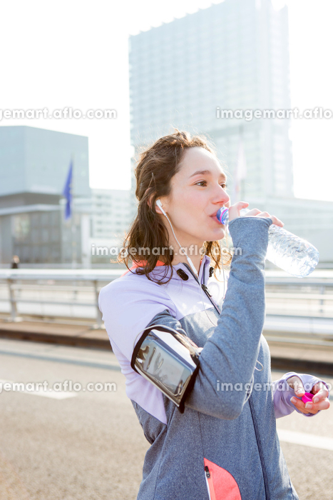 Woman drinking water during a running sessionの販売画像