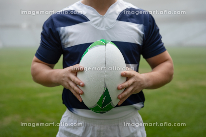 Mid section of Caucasian male rugby player holding a rugby ball in stadiumの販売画像