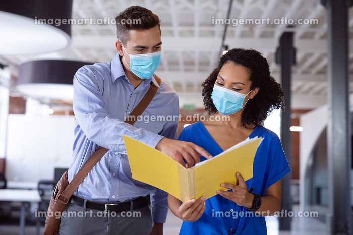 Diverse male and female colleague in face masks discussing paperwork in office corridor. working in business at a modern office during coronavirus covid 19 pandemic.の販売画像