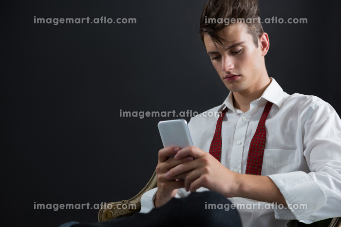Androgynous man sitting on chair and using mobile phoneの販売画像