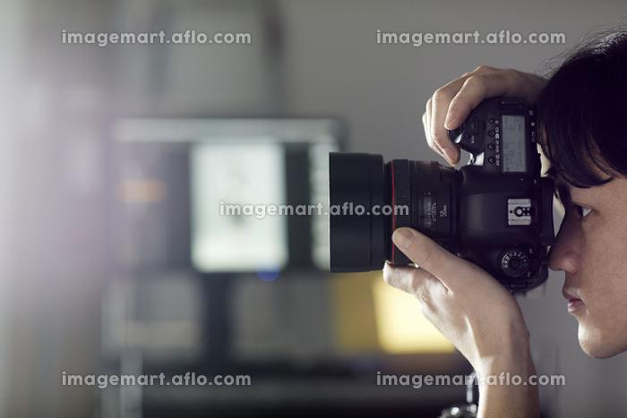 一眼レフカメラで撮影する日本人男性の販売画像