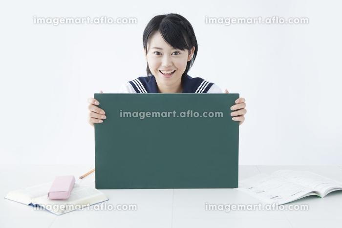 メッセージボードを持って微笑む女子中学生の販売画像