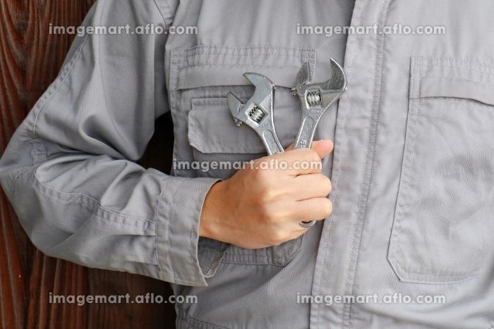 作業服を着た男性とモンキーレンチの販売画像