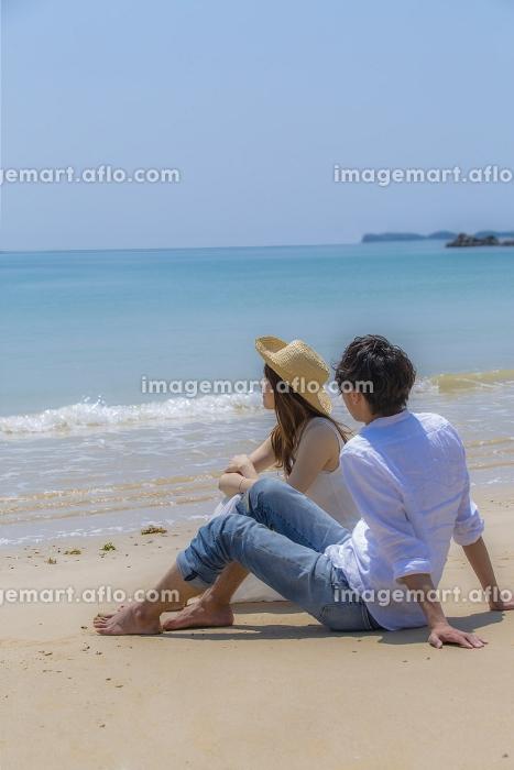 砂浜に座るカップルの販売画像