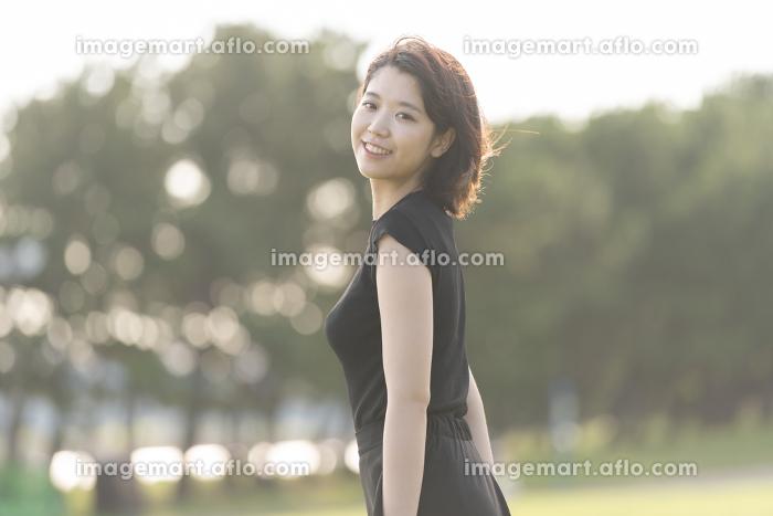 海沿いの公園を歩く若い女性
