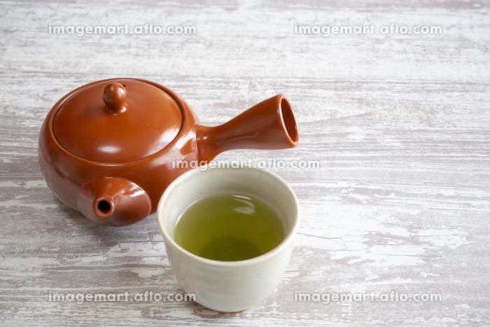 緑茶の入った湯呑みと茶色の急須の販売画像