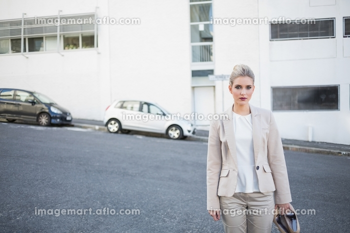 Serious stylish businesswoman holding her shoes outside on urban backgroundの販売画像