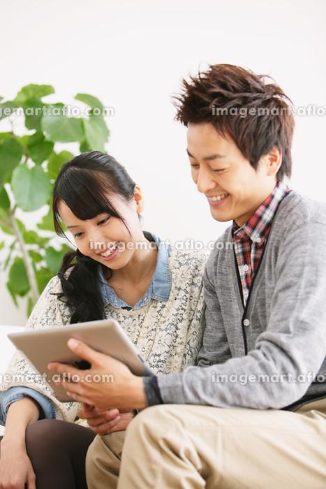 iPadを見るカップルの販売画像