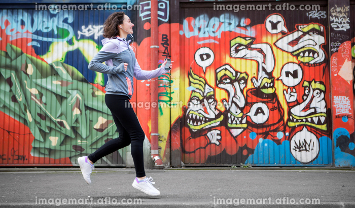 Young attractive woman running downtownの販売画像