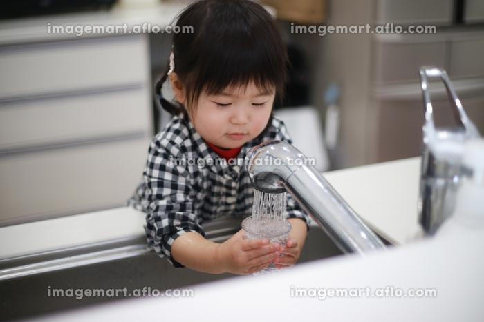 コップに水を注ぐ女の子の販売画像
