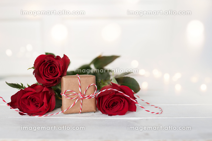 romantic red roses with a gift on white backgroundの販売画像