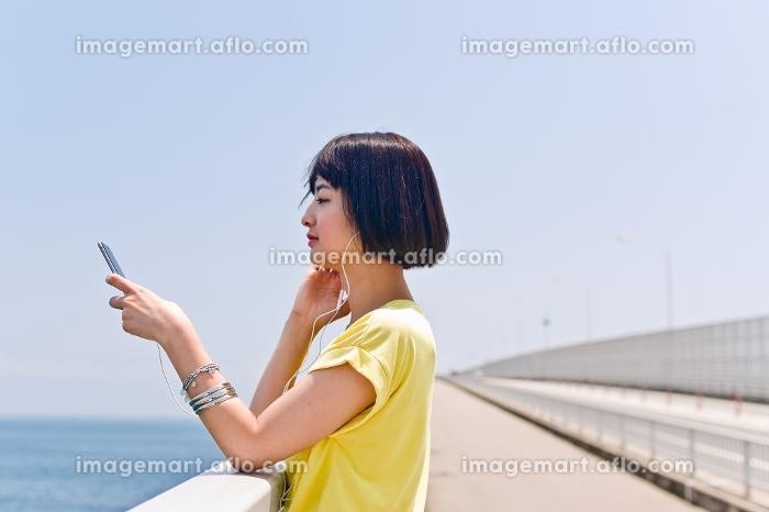 橋の上で音楽を聴く女性の販売画像