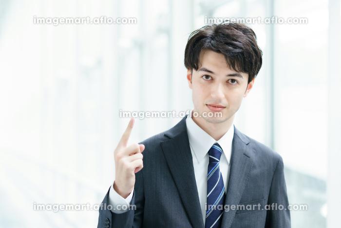 人差し指を立てるポーズをするビジネスマンの販売画像