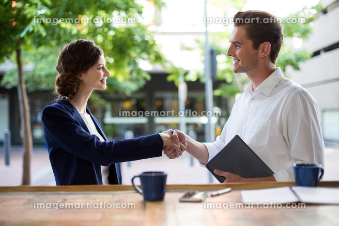 Businesswoman shaking hands with businessman at counterの販売画像
