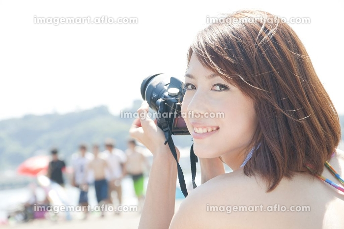 カメラを持って微笑む女性の販売画像