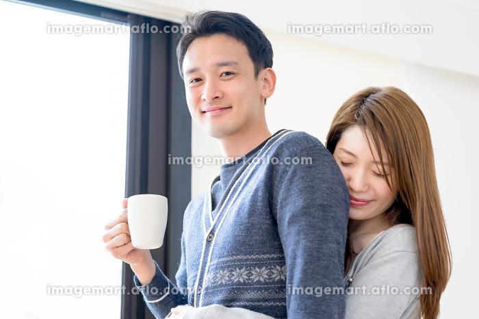 リビングで愛情表現をするカップルの販売画像