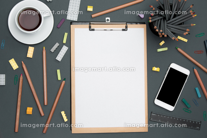 Office desk table with pencils, supplies, phone and cupの販売画像