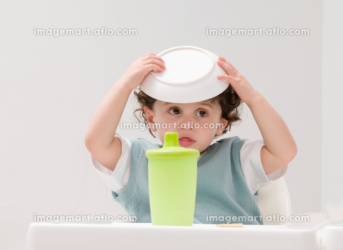 A boy with his food bowl on his head.の販売画像