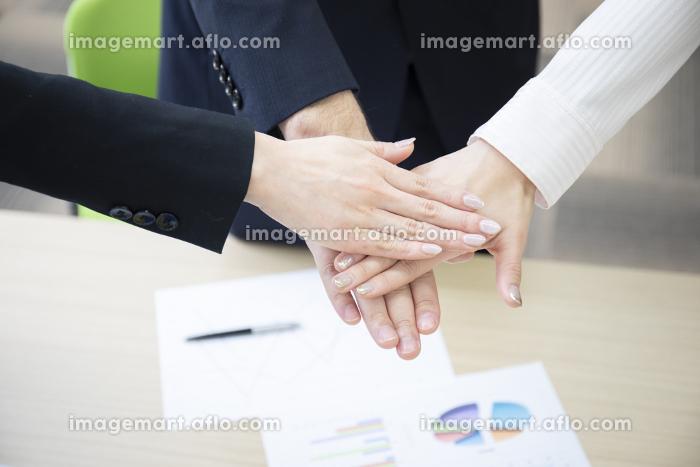 会議室にて3人のビジネスマンが手を合わせるの販売画像