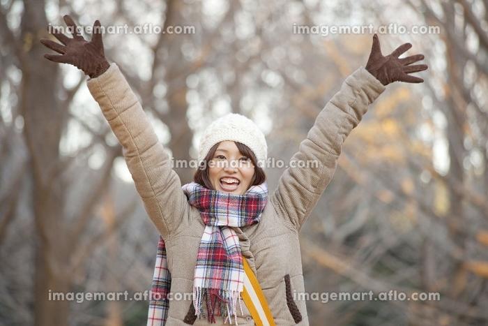 両手を高く上げる女性の販売画像