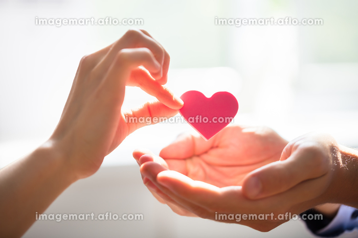 Woman Giving Heart On Man's Hand