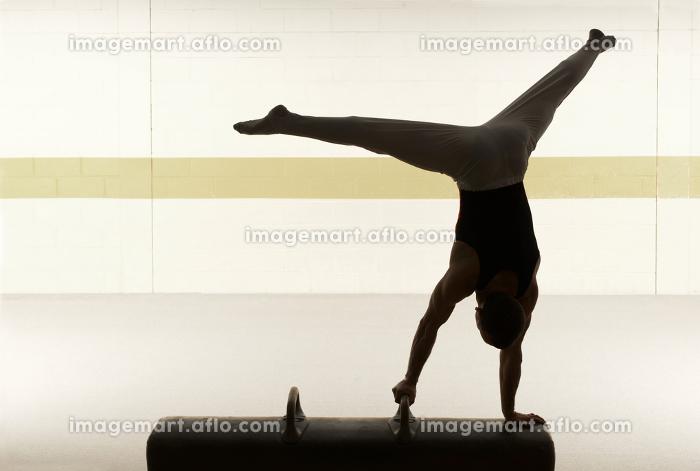 Male gymnast performing on pommel horseの販売画像