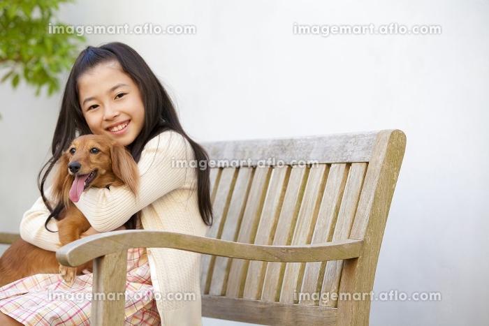 ミニチュアダックスフントを抱きしめる女の子