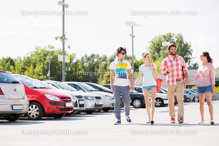 Happy friends walking on city street