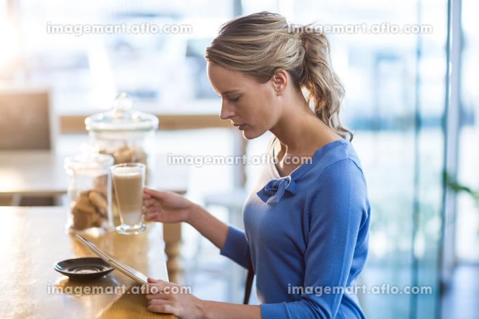 Woman using digital tablet in café