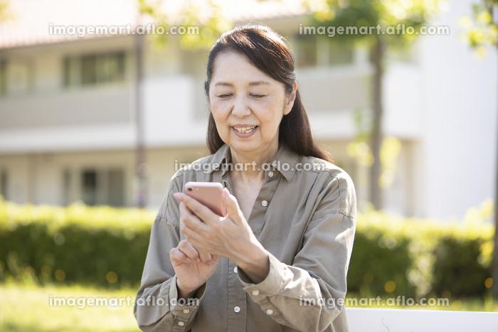 スマートフォンを操作するシニア女性の販売画像