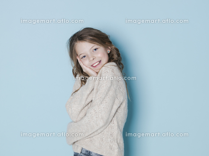 pretty and cool 9 year old girl with brown wool sweater posing in front of blue backgroundの販売画像