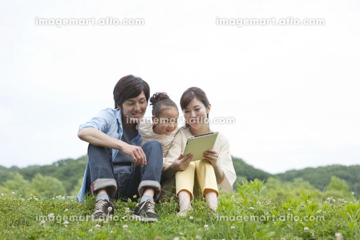 タブレットPCを見る家族3人の販売画像
