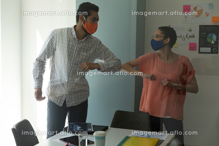 Mixed race man and woman wearing masks bumping elbows in greeting. hygiene in workplace during coronavirus covid 19 pandemic.の販売画像