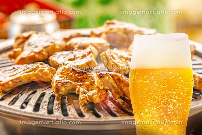 焼肉の背景と泡が垂れた水滴のついたグラスビールの画像の販売画像