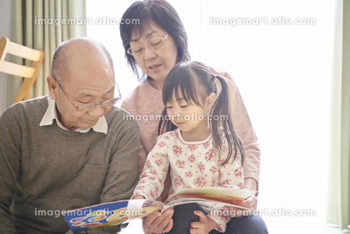 祖父母と絵本を読む女の子