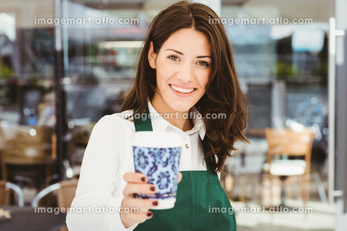 Smiling waitress serving a coffeeの販売画像
