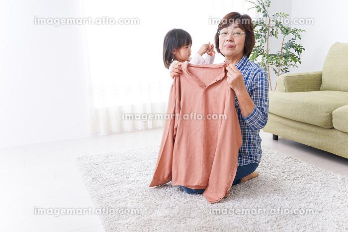 洗濯物をたたむおばあさんと子どもの販売画像