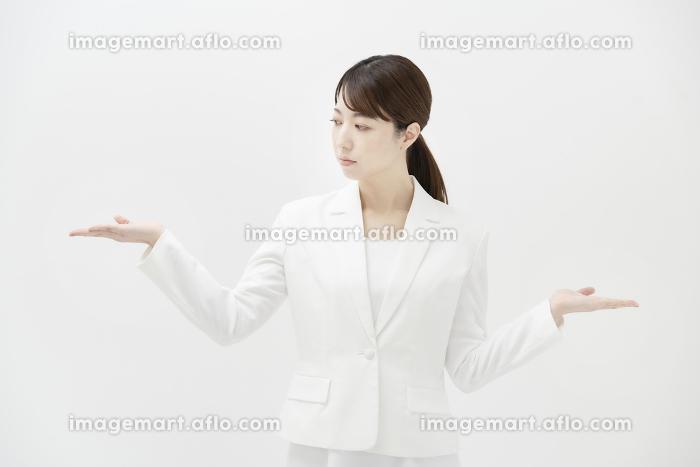 2つの選択肢を比較するようなポーズをするビジネスウーマンの販売画像