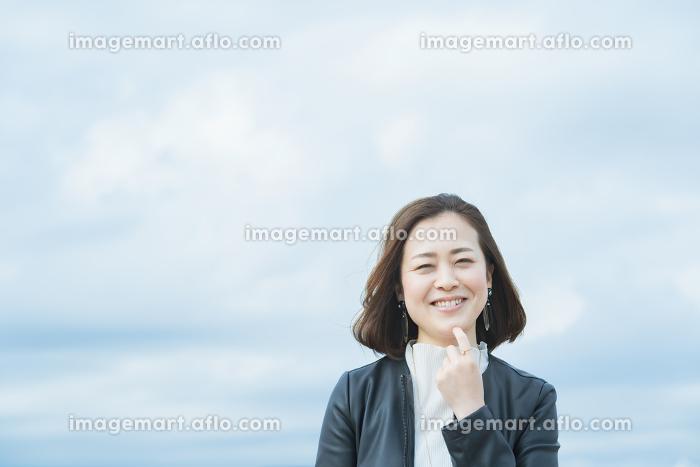 屋外で笑顔を見せるオフィスカジュアルスタイルの女性の販売画像
