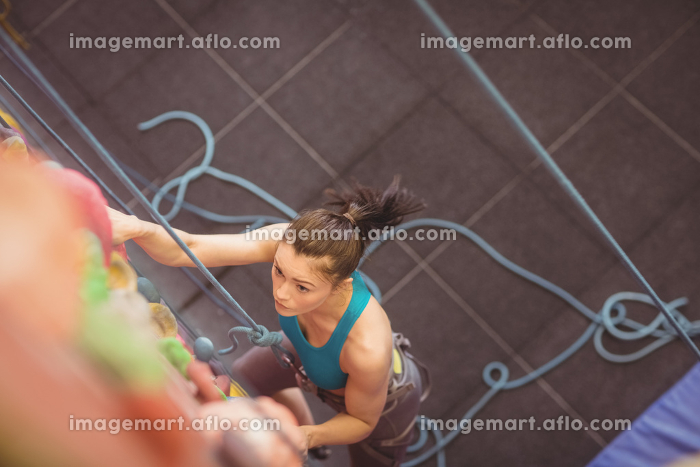 Woman climbing up rock wallの販売画像