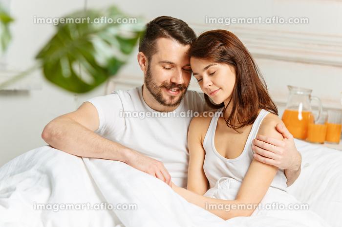 Young adult heterosexual couple lying on bed in bedroomの販売画像