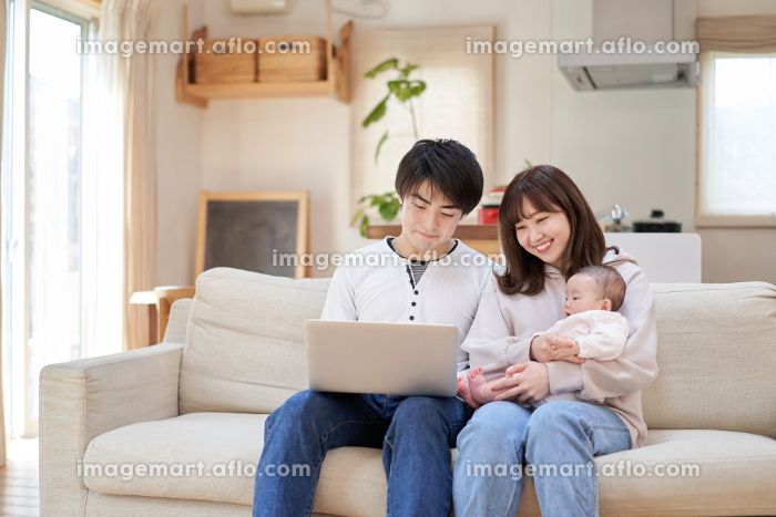 ソファでノートパソコンを見るアジア人ファミリーの販売画像