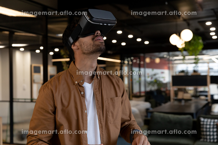 Mixed race businessman wearing virtual reality headset in creative office. technology and social distancing in business office workplace during covid 19 coronavirusの販売画像