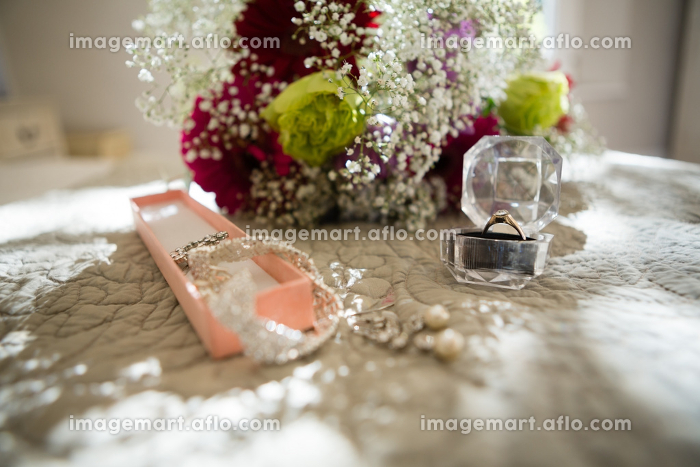 Close up of jewelry and bouquet on sofaの販売画像