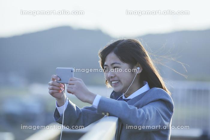 学校の屋上でスマートフォンを見る女子中学生